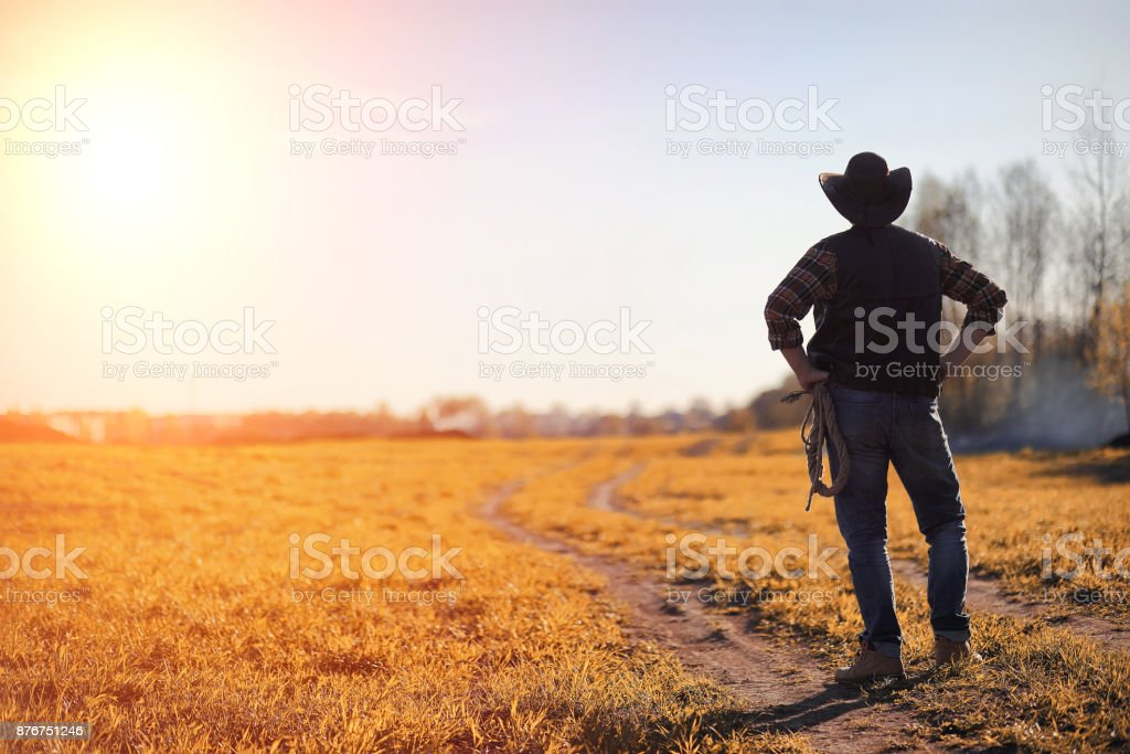A man cowboy hat and a loso in the field. American farmer in a f A man in a cowboy hat and a loso in the field. American farmer in a field wearing a jeans hat and with a loso. A man is walking across the field in hat Adult Stock Photo