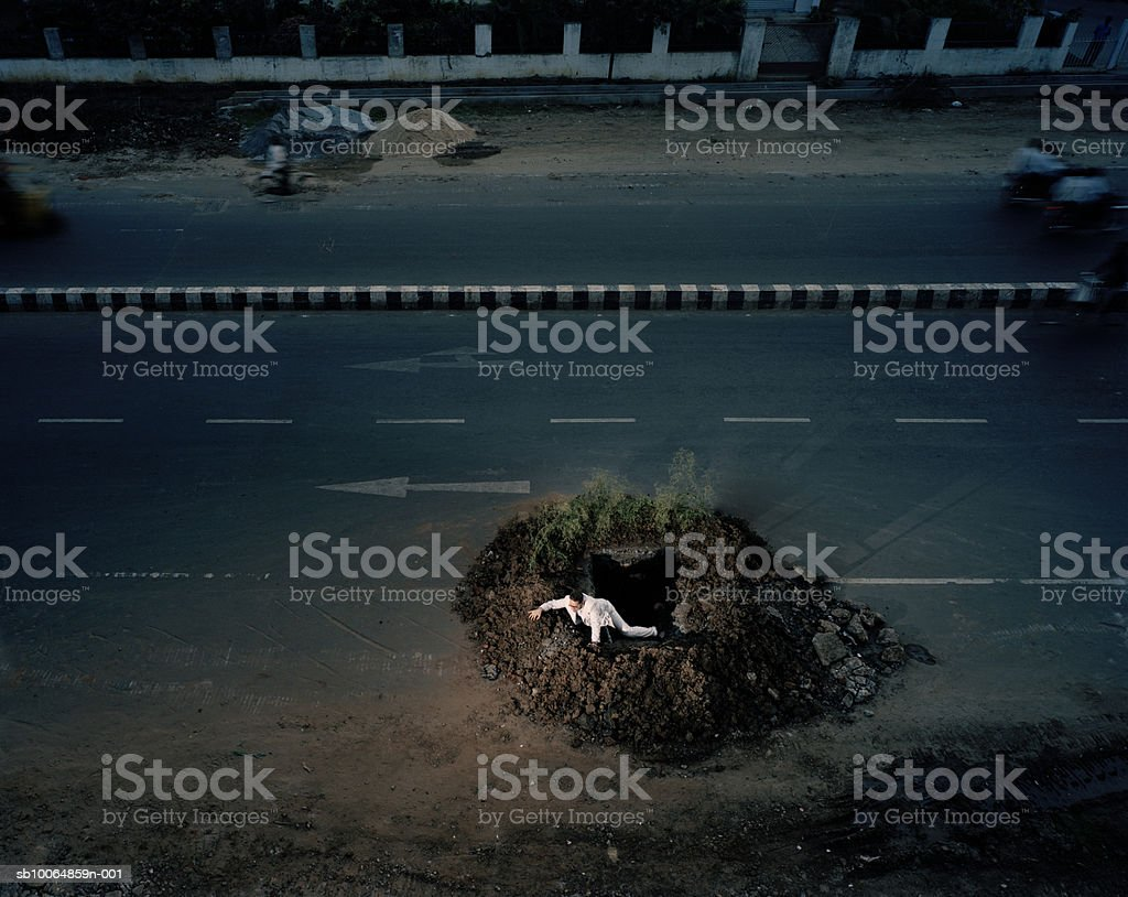 Man crawling out of hole in roadway, elevated view foto de stock libre de derechos