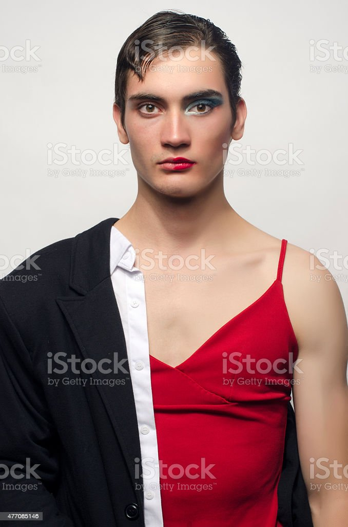 Man cross-dressing wearing a black suit and a red dress. stock photo