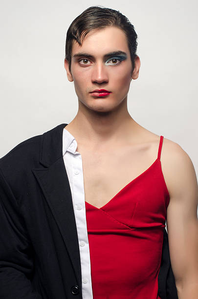 man cross-dressing wearing a black suit and a red dress. - transvestite stock photos and pictures