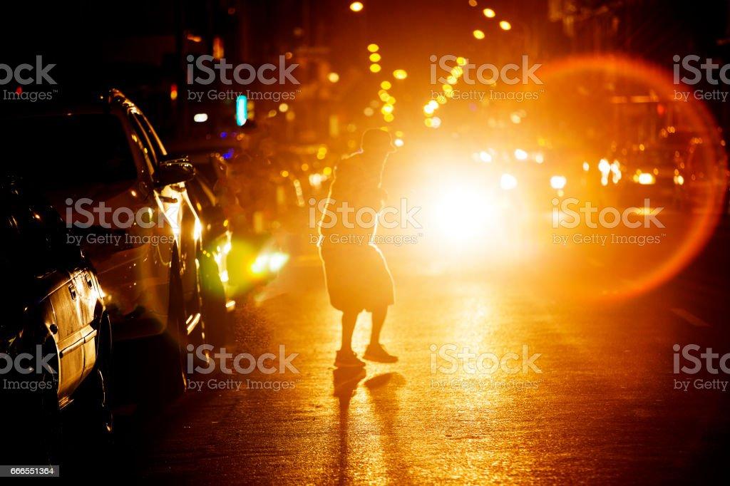L'homme traverse la route très fréquentée pendant la nuit - Photo
