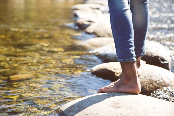 man crossing a river - scalzo foto e immagini stock