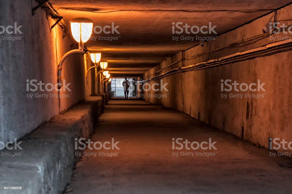 Man crossing a subterranean passage stock photo