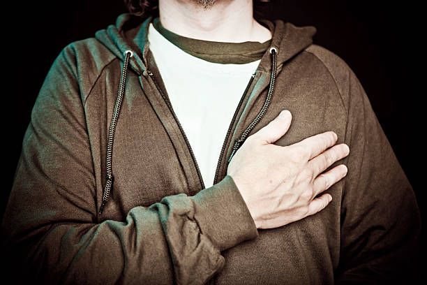 a man crossing his chest in patriotic pride - swearing stockfoto's en -beelden