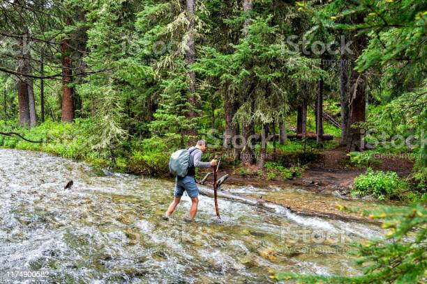 Man crossing river strong current ford on Conundrum Creek Trail in Aspen, Colorado in 2019 summer in forest woods
