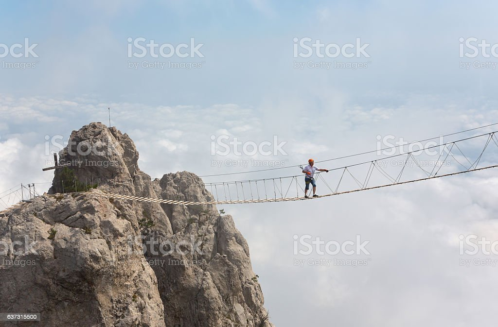 Man crossing the chasm stock photo