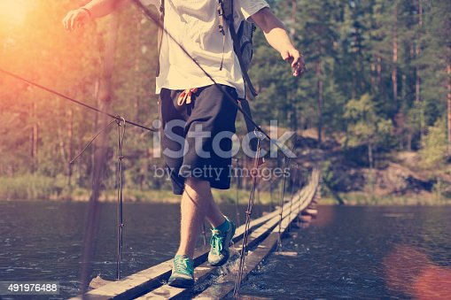 istock Man crossing through hanging bridge 491976488