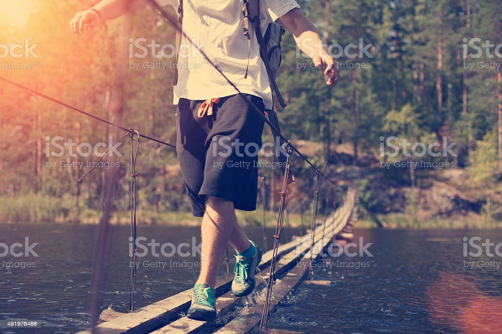 Man crossing through hanging bridge stock photo