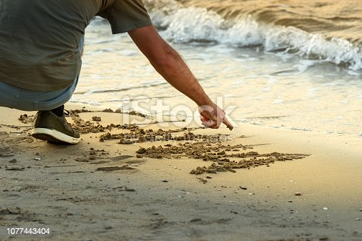 A man crouched down writing with his finger a message on the sand next to the sea at sunset, Rhodes, Greece.