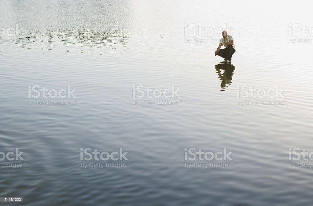 Homem Agachar-se na água foto de stock royalty-free