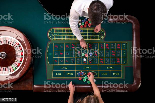 Man croupier and woman playing roulette at the table in the casino picture id907375012?b=1&k=6&m=907375012&s=612x612&h=mepft0uuldinhdstjghsr44rmjqktnedos ol3lztyi=