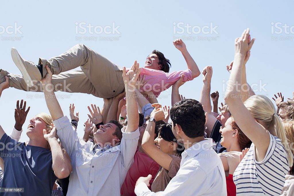 Man crowd surfing stock photo