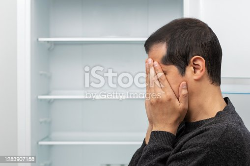 Close-up view of a man covering his face and crying with an empty refrigerator in the background in concept of economic crisis and copy space