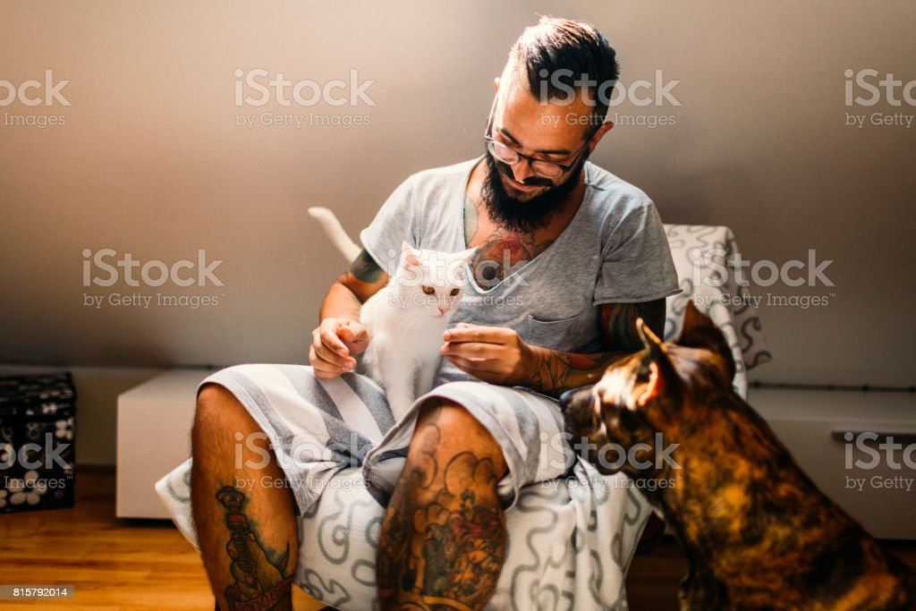 Man cuddling with his cat and his dog stock photo