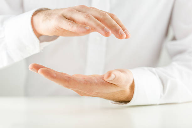 Man cupping his hands in a protective gesture Man cupping his hands in a protective gesture above and below an empty space for your product placement or conceptual object, close up view of the hands against a white shirt. hands cupped stock pictures, royalty-free photos & images