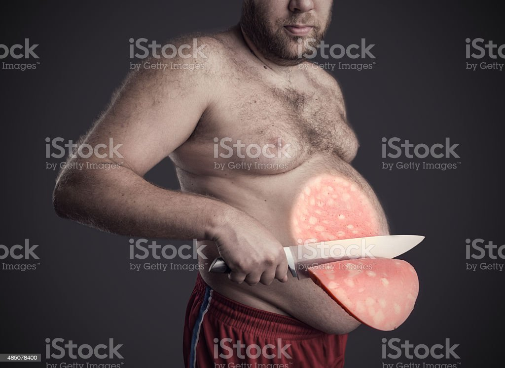 Man cuts a slice of sausage from his belly stock photo