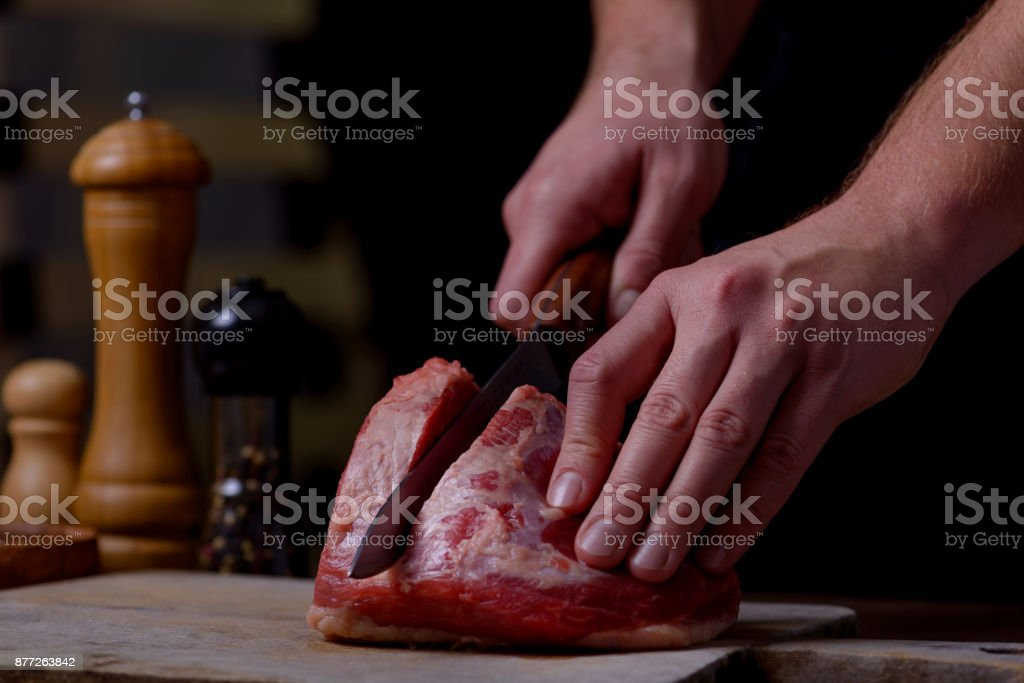 Man cuts beef meat on cutting board stock photo