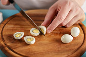 Man cuts boiled quail eggs on wooden cutting board close-up.