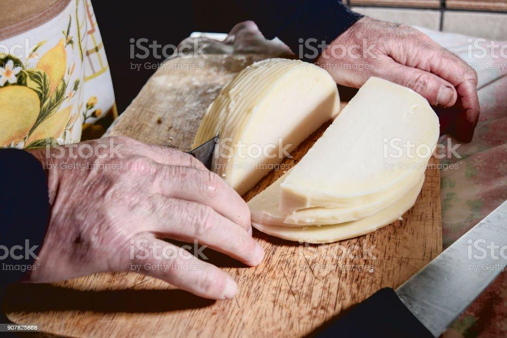 man cuts cheese stock photo