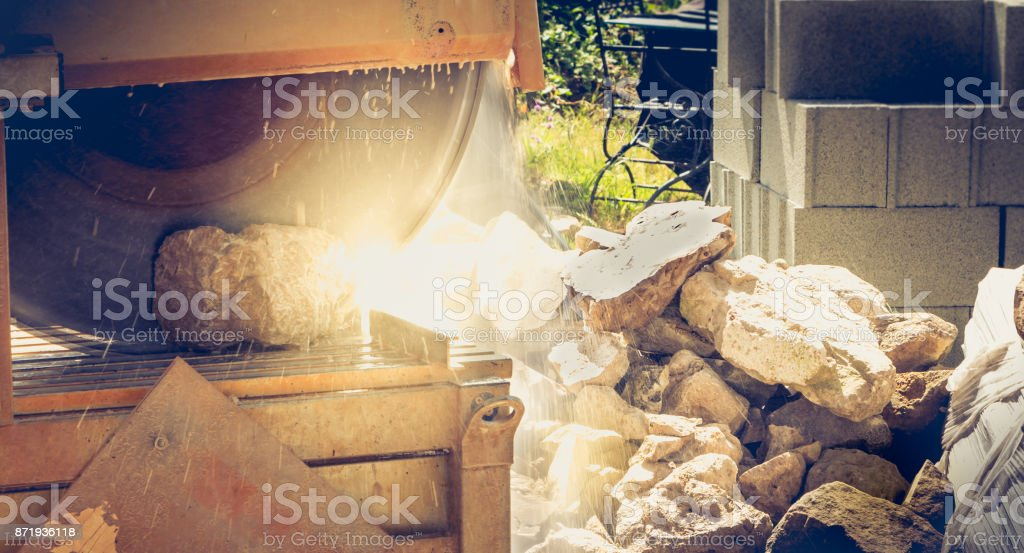 man cutting a stone with a water saw stock photo
