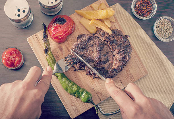 Man cutting and eating a grilled beef steak stock photo
