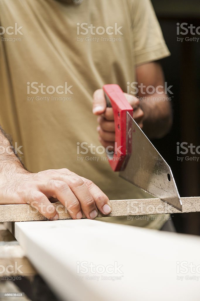 Man cutting board with hand saw royalty-free stock photo