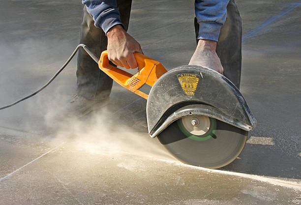 Man cutting control groove in concrete slab stock photo