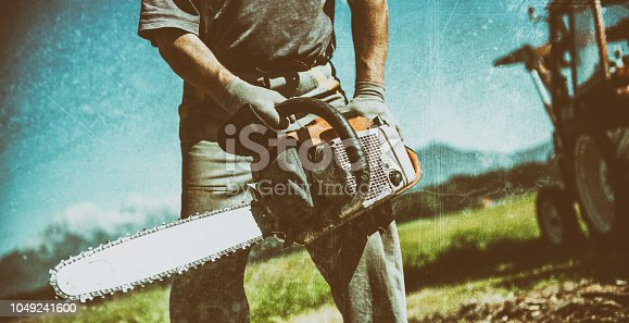 Man Cutting Firewoods With Electric Chainsaw