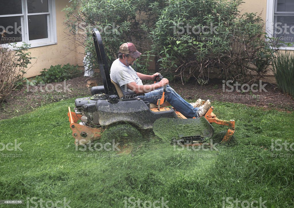 Man cutting grass on lawnmower stock photo