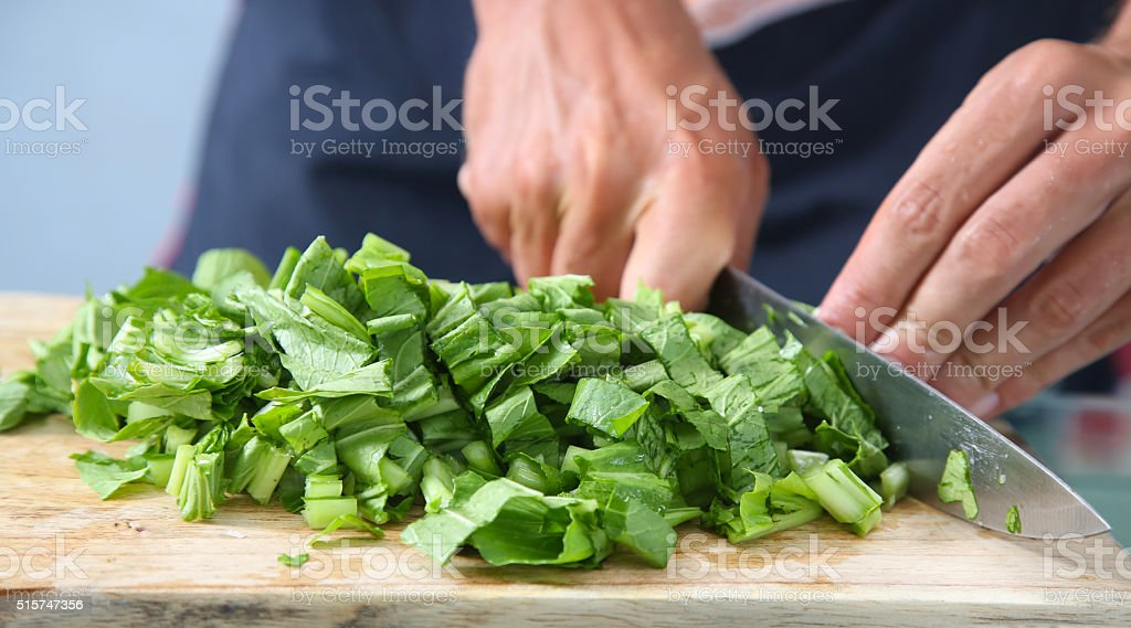 Man cutting green salad on the wooden board stock photo