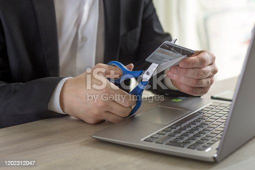 Business man cutting credit card with scissors