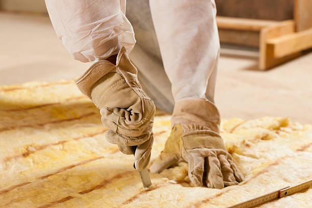 Man cutting insulation material for building construction stock photo
