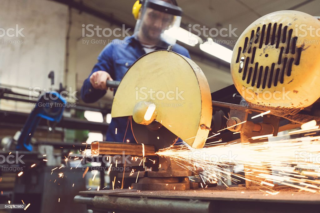 Man cutting metal bar in a workshop, using grinder stock photo