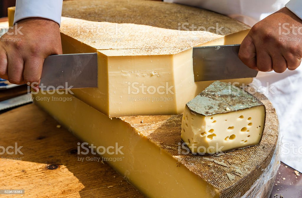 Man cutting piece of cheese stock photo