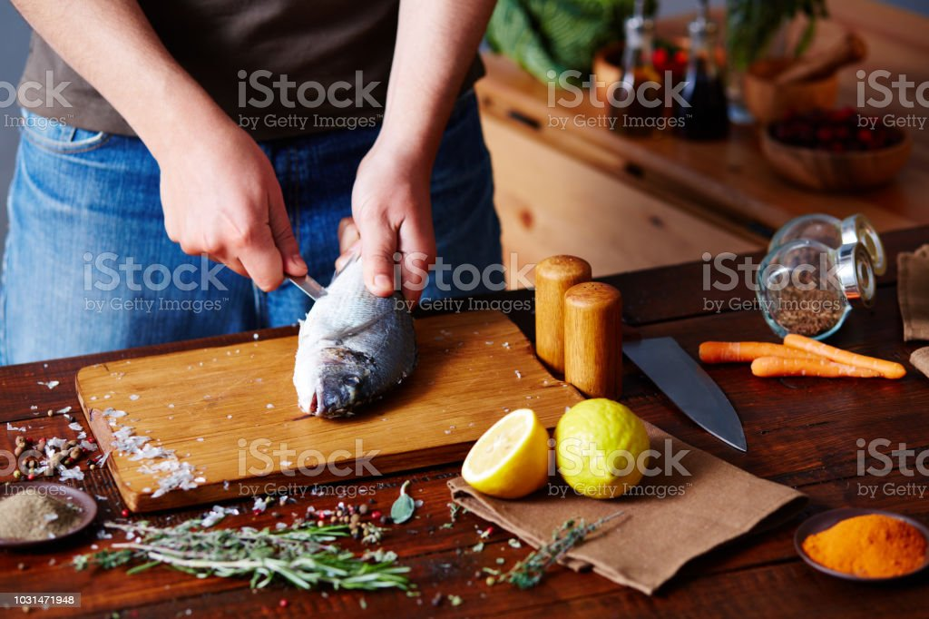 Man Cutting Raw Trout stock photo