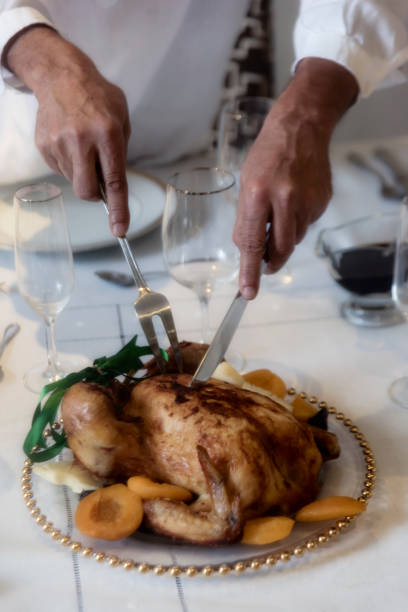 Man cutting roated chicken New Year`s Eve in Brazil. Man dressing white cutting a roasted chicken or turkey. Close-up of man`s hands cutting meat. reveillon stock pictures, royalty-free photos & images