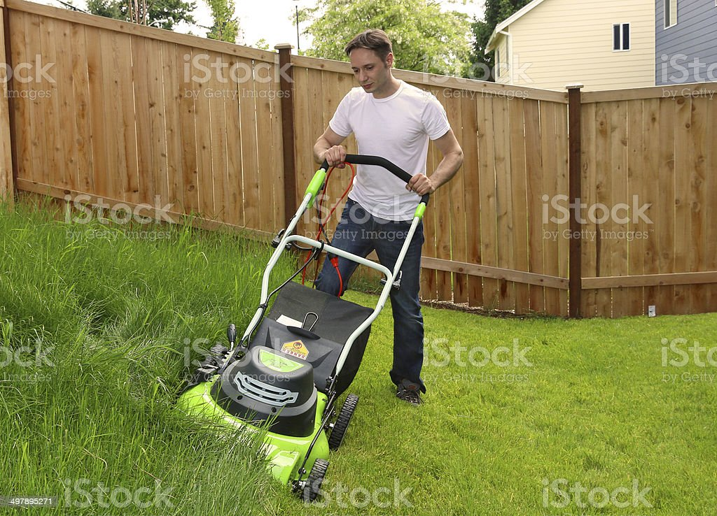 Man cutting the grass with lawn mower stock photo