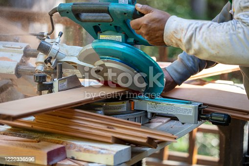 Man cutting wood with radial arm saw.