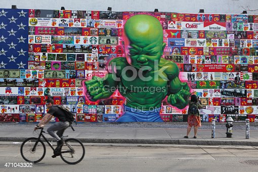 istock Man cycles past huge colorful mural on Houston Street NYC 471043302