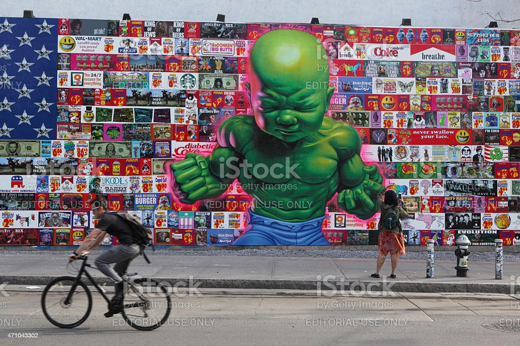 Man cycles past huge colorful mural on Houston Street NYC stock photo