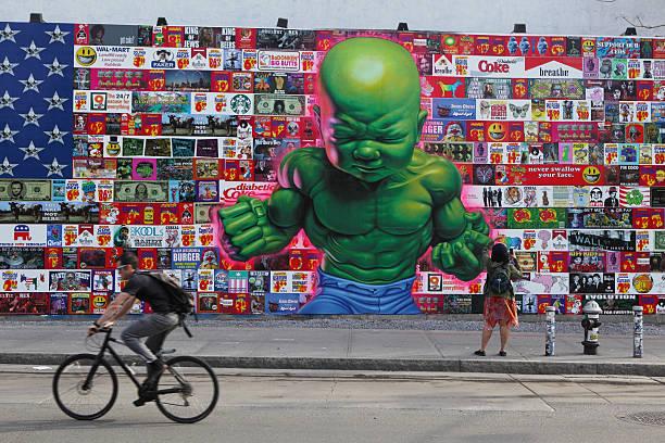 mann hz vergangenheit riesige farbenfrohe wandmalereien auf der houston street in nyc - schlechte laune sprüche stock-fotos und bilder