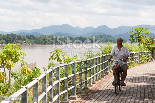 Chiang Khan, Thailand - October 12th 2010: A man cycling along the Mekhong riverbank Laos on the other side of the river. The river forms the border with Laos in this area.