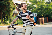 Handsome man on a bike using smartphone searching around