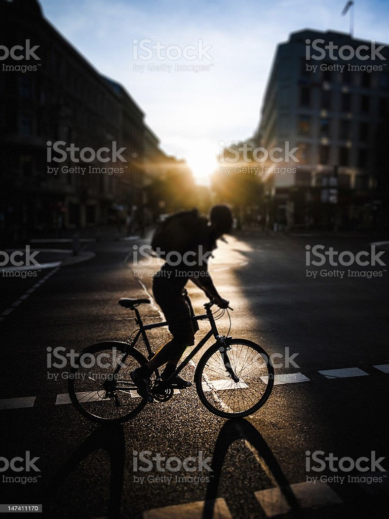 Man cycling at sunset in the city royalty-free stock photo