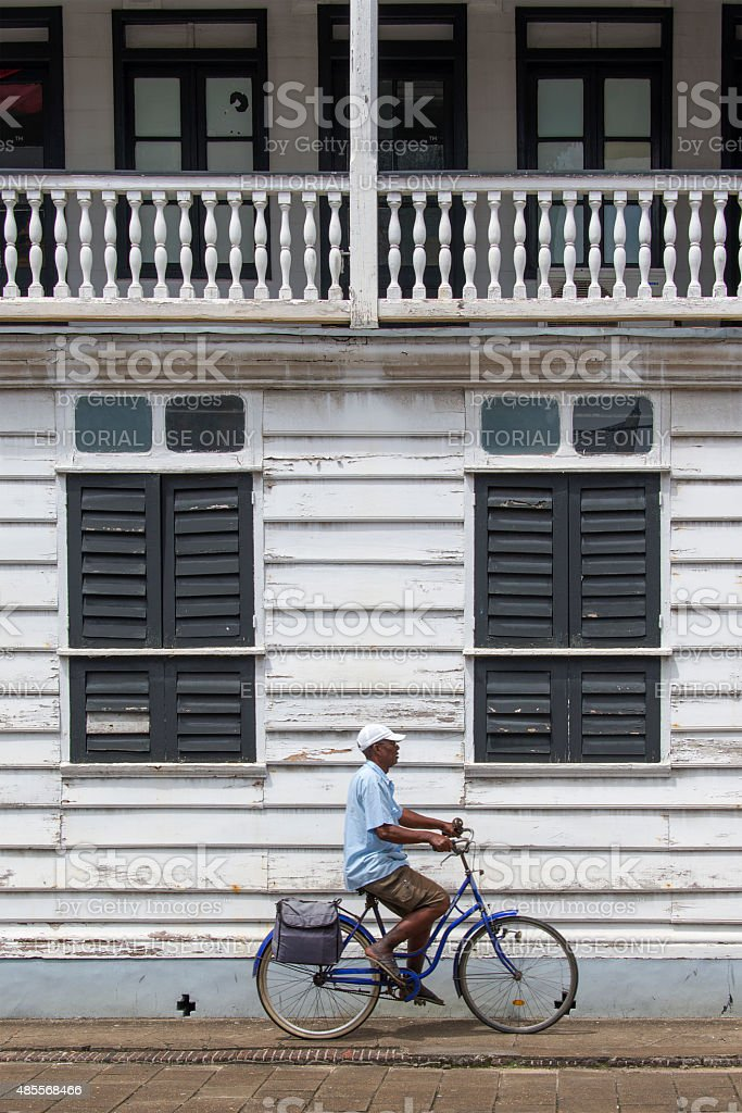 Man cycling in front of a white wooden historic building stock photo
