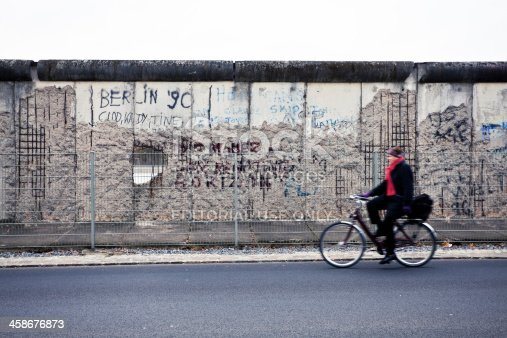 Berlin, Germany - November 16, 2011: Man cycling along the last remains of the Berlin wall along the ex headquarters of the Gestapo and the SS in Niederkirchnerstrasse.