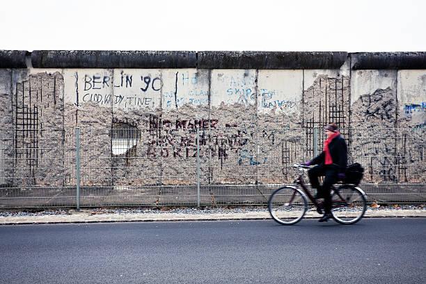 mann, radfahren in der vorderseite der berliner mauer, east side, deutschland - trennungssprüche stock-fotos und bilder