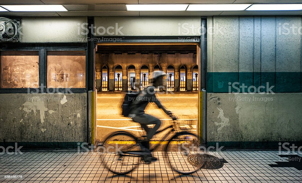 Man cycling in the night in downtown Osaka city streets stock photo