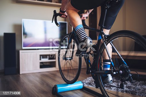 Unrecognizable man cycling indoor with exercise bike trainer.
