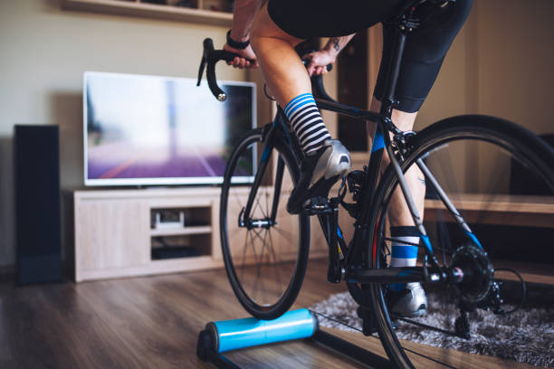 Man Cycling Indoor With Exercise Bike Trainer.